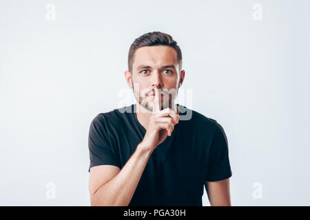 Young man holding index finger on lips asking for silence.  Secret concept - Stock Photo