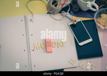 Messy office desk depicting life at a busy office, chasing deadlines and the working millennial life - Stock Photo
