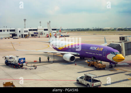 Bangkok, Thailand - 20 February 2018: Refueling aircraft at aerodrome. Aviation tanker truck refuels passenger plane - Stock Photo
