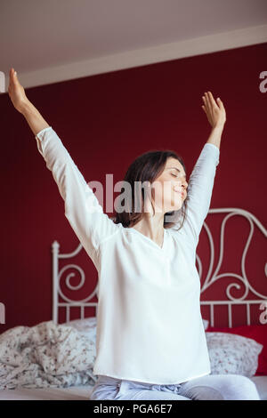 Portrait of pretty woman stretching in bed after wake up. Good morning concept - Stock Photo