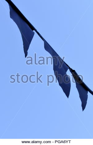 Spain, Andalusia, Costa del Sol, Frigiliana, August. Festival of 3 cultures.  Medieval pennants flutter in the breeze set against the deep blue sky - Stock Photo