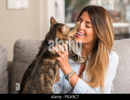 Young beautiful woman smiling and playing with cat on the sofa. - Stock Photo