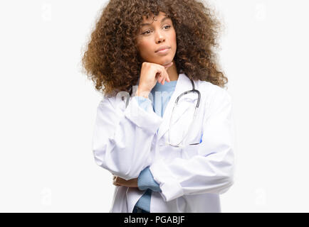 African american doctor woman, medical professional working thinking and looking up expressing doubt and wonder - Stock Photo