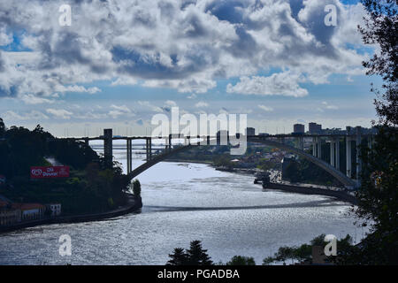 Sunlight reflecting in the Douro river in Porto, Ponte da Arrábida casting shadows on the water. - Stock Photo