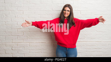Young brunette woman standing over white brick wall looking at the camera smiling with open arms for hug. Cheerful expression embracing happiness. - Stock Photo