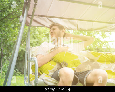 young bearded man sitting relaxing on the garden swing sofa on a summer day - Stock Photo