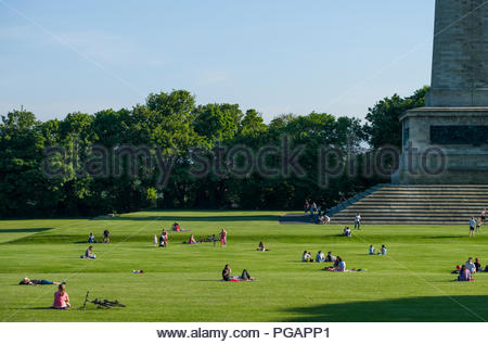 Many people sitting in groups on the green lawn enjoying the afternoon sunshine at the Wellington Monument in Phoenix Park, Dublin, Leinster, Ireland - Stock Photo