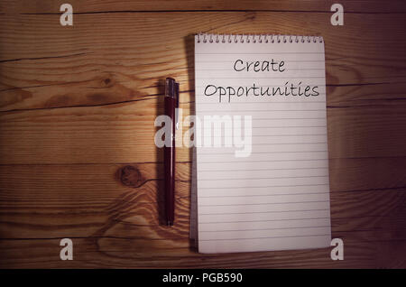 Spiral notebook on a wooden table with a message handwritten in the first page. - Stock Photo