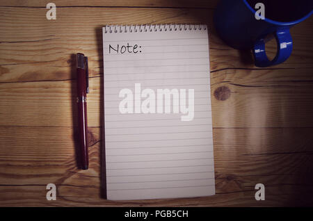 Notebook on the table with words written on one page with pen and coffee mug on both sides - Stock Photo
