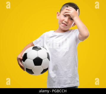 Dark haired little child playing with soccer ball stressed with hand on head, shocked with shame and surprise face, angry and frustrated. Fear and ups - Stock Photo