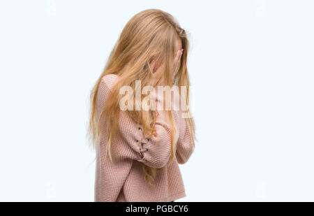 Blonde teenager woman wearing pink sweater with sad expression covering face with hands while crying. Depression concept. - Stock Photo