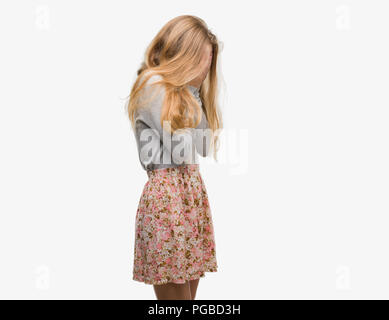 Blonde teenager woman wearing flowers skirt with sad expression covering face with hands while crying. Depression concept. - Stock Photo