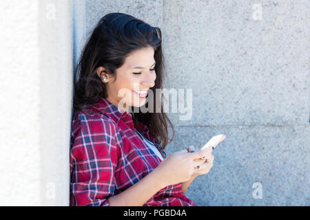 Caucasian woman in casual clothes sending message outdoors in the summer - Stock Photo