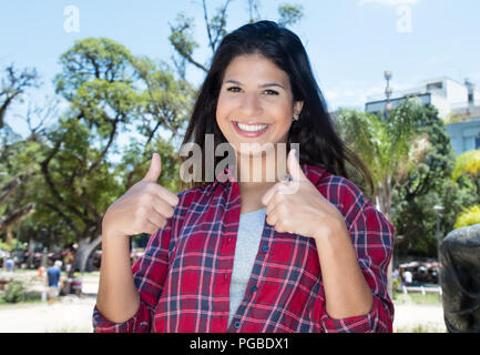 Caucasian woman with hipster shirt showing both thumbs outdoors in summer in city - Stock Photo