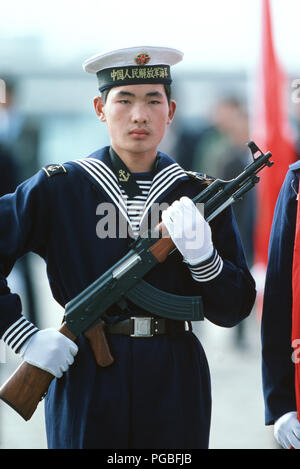 A Chinese sailor, armed with a Type 56 assault rifle, stands watch during a welcoming ceremony given in honor of the first US Navy (USN) ships to visit China in 40 years. - Stock Photo