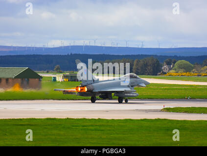 An RAF Lossiemouth Eurofighter FRG4 on a QRA take off with glowing afterburner tail pipes. - Stock Photo