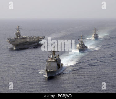 The US Navy (USN) Ticonderoga Class Guided Missile Crusier USS MOBILE BAY (CG 53) (front), Arleigh Burke Class Guided Missile Destroyers USS RUSSELL (DDG 59) and USS SHOUP (DDG 86) (right) perform a pass and review with the USN Nimitz Class Aircraft Carrier USS ABRAHAM LINCOLN (CVN 72) in the South China Sea. - Stock Photo