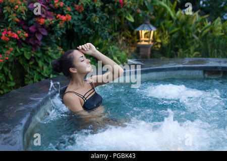 Young woman relaxing in jacuzzi spa in luxury hotel - Stock Photo