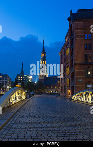 Bridge with cobblestones and Hauptkirche Sankt Katharinen at night, Speicherstadt, district in the Hafencity quarter, port of Hamburg, Germany - Stock Photo