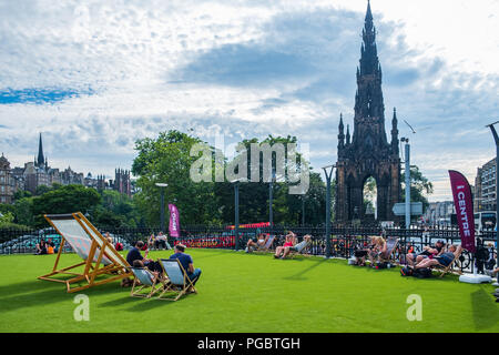 Edinburgh, United Kingdom - July 27, 2018: People enjoying the sun on lounge chairs near Scott Monument on Princes Street in Edinburgh on a hot summer - Stock Photo