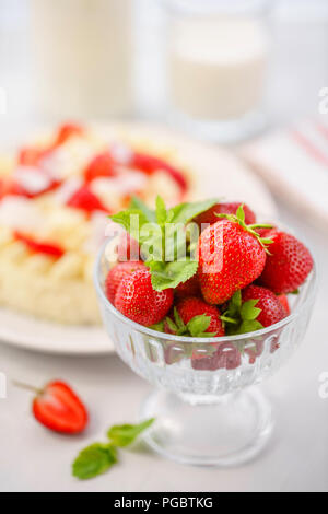 focus on strawberries . Delicate strawberry cheesecake with coconut. Delicious homemade cake with Fresh berries on light table. - Stock Photo
