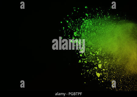Freeze motion of colorful powder explosion isolated on black background. Colored dust splatted. - Stock Photo