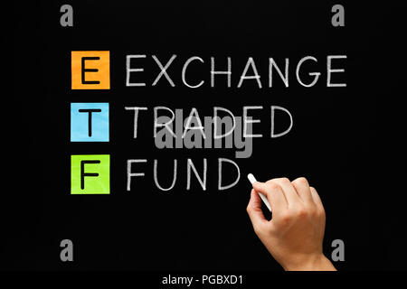 Hand writing ETF - Exchange Traded Fund with white chalk on blackboard. - Stock Photo