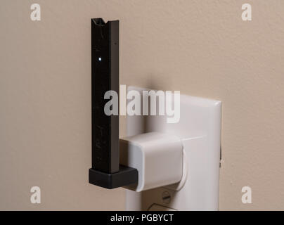 Juul nicotine vapor dispenser charging in USB charger - Stock Photo