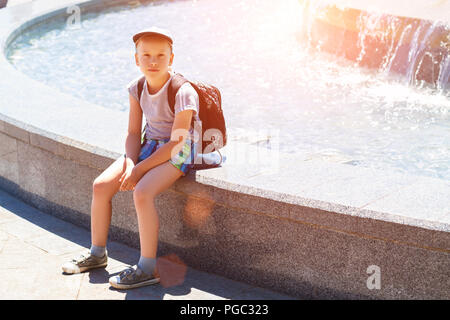 boy sitting by the fountain on a Sunny day - Stock Photo