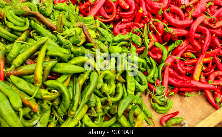 Pointed red and green peppers, in vivid contrast colours, displayed on food market. - Stock Photo