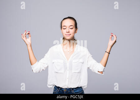 Restful peaceful blonde female feels relaxed, stands in lotus pose, tries to concentrate or to be focused, closes eyes, enjoys silence, tries to find  - Stock Photo
