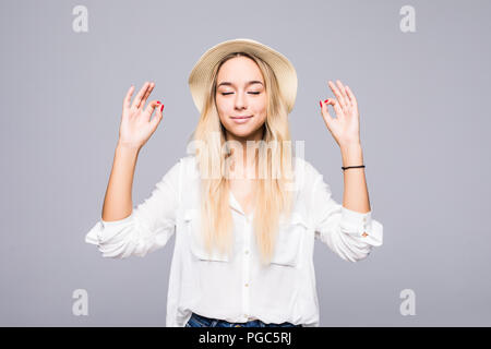 Restful peaceful woman in straw hat feels relaxed, stands in lotus pose, tries to concentrate or to be focused, closes eyes, enjoys silence, tries to  - Stock Photo