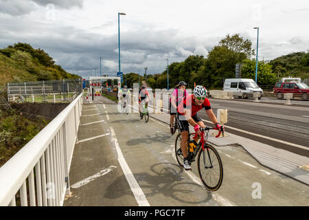 Cyclists using the other traffic lane to cross the M48 Severn Bridge from England into Wales. UK - Stock Photo