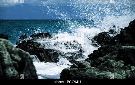 wave breaking on a rock. The speed of capture allows to see the drops in detail. - Stock Photo
