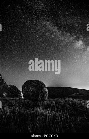 Beautiful view of starred night sky with milky way over a cultivated field with hay bale - Stock Photo