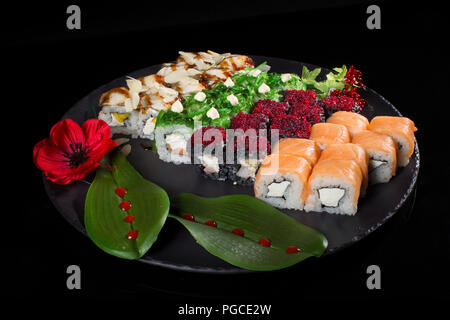 Seth sushi on a black background.Menu of the Japanese restaurant. Several sushi lined on a plate decorated with a decor of red berries, a flower and l - Stock Photo