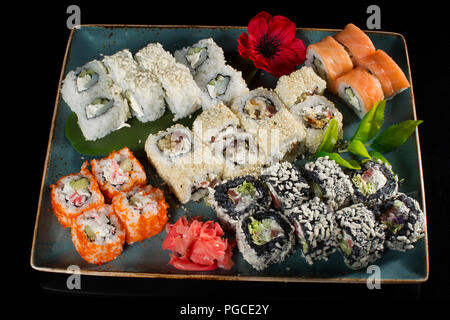 Menu of the Japanese restaurant. Several sushi laid out on a plate with ginger sauce wasabi. Rolls from above - Stock Photo