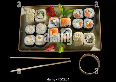 Menu of the Japanese restaurant. Several sushi lined on a plate with bamboo sticks and soy sauce.View of the rolls from above - Stock Photo