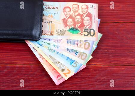Money from Ghana in the black wallet - Stock Photo