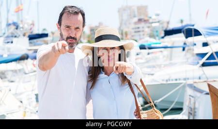 Middle age couple in marina pointing with finger to the camera and to you, hand sign, positive and confident gesture from the front - Stock Photo