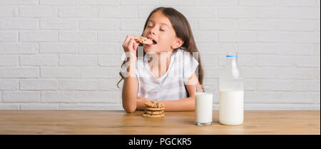 Young hispanic kid sitting on the table drinking milk and eating chocolate cooky with a confident expression on smart face thinking serious - Stock Photo