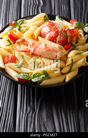 Italian penne pasta with seafood lobster meat, tomatoes and herbs close-up on a plate on a table. vertical - Stock Photo