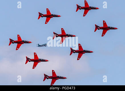Dunsfold, Surrey, UK. 25th Aug 2018. A commercial aircraft departing London's Gatwick Airport appears to join in with the RAF Red Arrows Display team performing at the Wings and Wheels aircraft and motoring display taking place at Dunsfold in Surrey, England over this weekend. Credit: Trevor Payne/Alamy Live News - Stock Photo