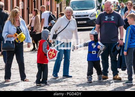 Haddington, Scotland, UK. 25th August 2018. Haddington 700 Celebrations Medieval Big Day, The Medieval Day is the highlight of Haddington 700 events taking place in 2018 to celebrate the granting of a charter by Robert the Bruce to the town in 1318, confirming Haddington's right to hold a market and collect customs. Events across the market town included Medieval children's games, a parade and the main event on East Haugh with marquees, funfair, and bands. Two little boys dressed in Medieval costume have fun fighting with swords - Stock Photo