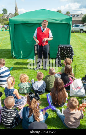 Strathaven, Scotland, UK. 25th August, 2018. A magician entertaining the kids at the Strathaven Balloon Festival celebrating its 20th Anniversary and is held in the award winning John Hastie Park. Credit: Skully/Alamy Live News - Stock Photo