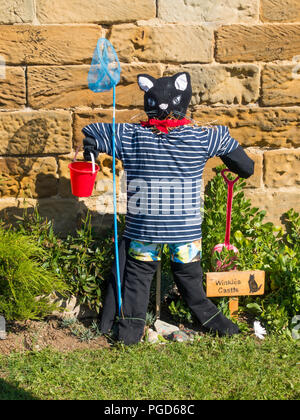 Marske North Yorkshire August 25th/ Like many Yorkshire villages Marske by the Sea has a weeklong Scarecrow Festival which started today 25th August,  many different organisations and social groups have made scarecrows an erected them around the village.  Parents and children can get a trail map to follow and view all the exhibits.  There is a prize draw at the end of the week. This cat is by the local Folk Museum  Winkies Castle in a former cobblers shop it had a cat called Winkie Credit: Peter Jordan NE/Alamy Live News - Stock Photo