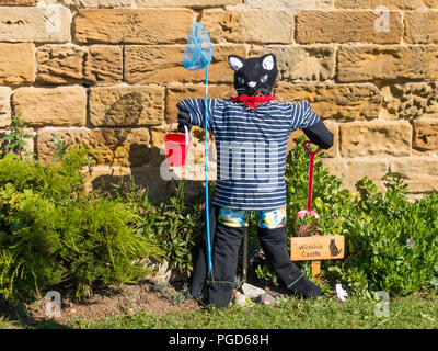 Marske North Yorkshire August 25th/ Like many Yorkshire villages Marske by the Sea has a weeklong Scarecrow Festival which started today 25th August,  many different organisations and social groups have made scarecrows an erected them around the village.  Parents and children can get a trail map to follow and view all the exhibits.  There is a prize draw at the end of the week. This cat is by the local Folk Museum  Winkies Castle in a former cobblers shop it had a cat called Winkie' Credit: Peter Jordan NE/Alamy Live News - Stock Photo