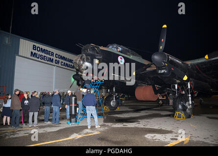 Nanton, Canada. 24th August, 2018.  Bomber Command Museum of Canada visitors line up for a Lancaster cockpit tour. The event is part of a 75th anniversary commemoration of the Dambusters Raid during World War II. Rosanne Tackaberry/Alamy Live News - Stock Photo