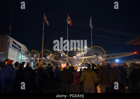 Nanton, Canada. 24th August, 2018. Visitors at the Bomber Command Museum of Canada watch as a Lancaster Bomber is started up during a night engine run. The event is part of a 75th anniversary commemoration of the Dambusters Raid during World War II. Rosanne Tackaberry/Alamy Live News - Stock Photo