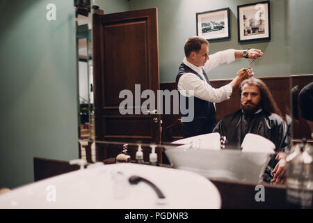 Barbershop with wooden interior. Bearded model man and barber. - Stock Photo